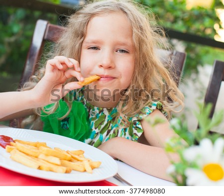 Ð¡hild eating potato chips in the cafe. Fast food. - stock photo