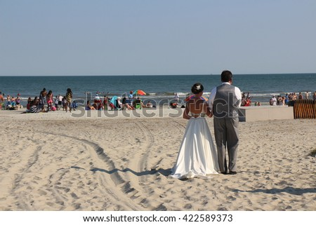 Hilton Head Island, South Carolina on 8 May 2016  rear view bride and groom on white sand beach