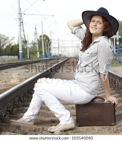 Hippie girl with retro suitcase on the railway Beautiful young blonde woman walking on railroad tracks with suitcase and cowboy hat - stock photo