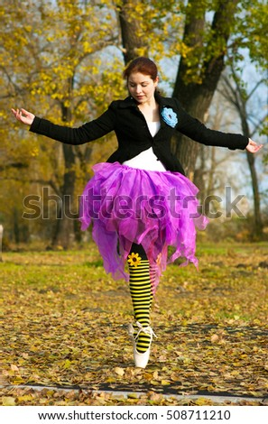 Hipster Ballerina dancing in autumn park