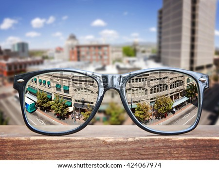 hipster glasses on a park bench or table with a cityscape in the background - stock photo