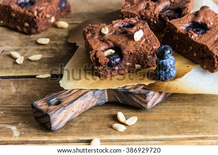 ?hocolate brownie with peanuts, blueberries on a wooden table - stock photo