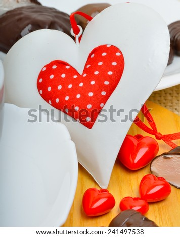 Ã?Â??hocolate candies and a valentine heart on white plate on wooden background. - stock photo