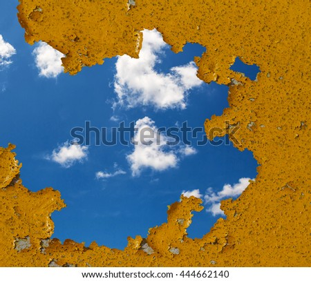hole in  wall with peeling orange color and Blue sky