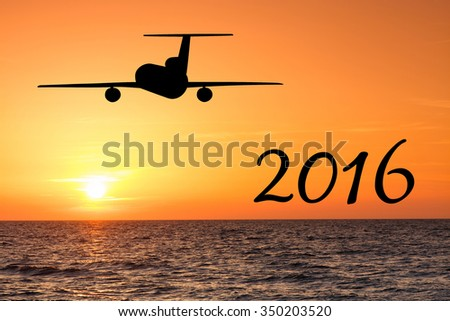 2016 holiday concept. Airplane and sunset over the sea