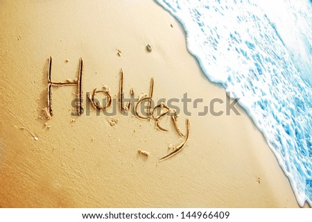 """Holiday"" written in sand beach"
