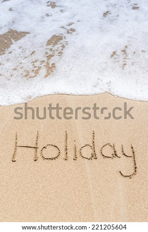 """""""Holiday"""" written in the sand on the beach  - stock photo"""
