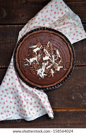 homemade dark chocolate tart  on rustic background - stock photo