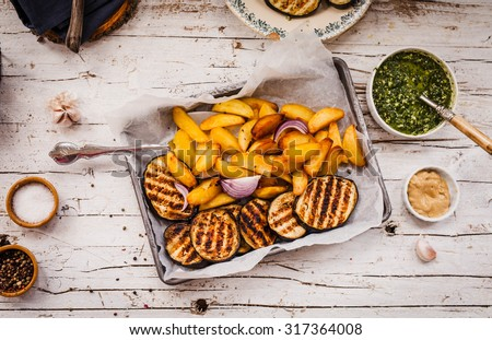 Homemade fried potatoes.The Perfect finger food for cottage fries potatoes and BBQ eggplant slices and plate of pesto and mustard sauce. Rustic style from above  - stock photo