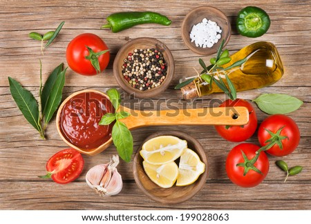 homemade tomato sauce in a wooden spoon on brown table and ingredients
