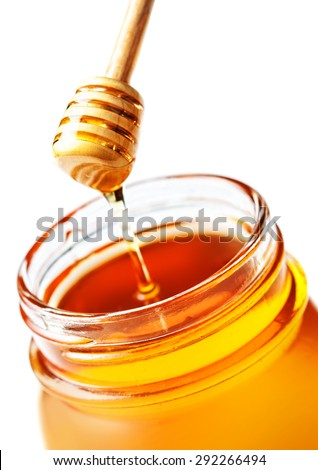 Honey Dipping with honey in glass jar isolated on white background macro. Wooden honey dipper close up.  - stock photo