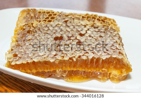 Honey in honeycomb  in plate on wooden table