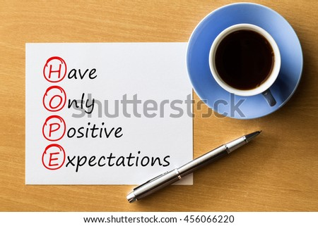 (HOPE) Have only positive expectations - handwriting on notebook with cup of coffee and pen, acronym business concept