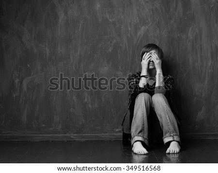 Hopeless woman is sitting against the wall, her face is closed by her hands. Black and white - stock photo
