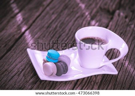 Hot coffee, macarons on an old wooden floor.