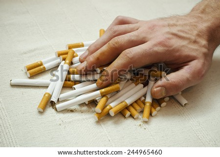 Human hand with stained fingers on a pile of cigarettes.