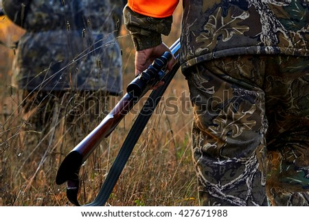 Hunter in camouflage clothes  with hunting rifle. Hunting in the forest - stock photo