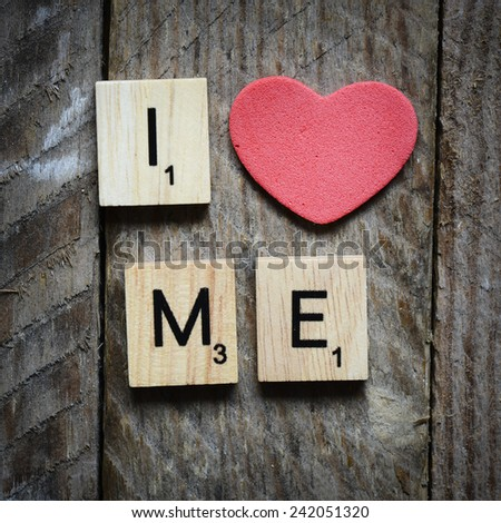 I love me Concept. Red heart and Wooden Scrabble letters spelling I love me Concept. - stock photo