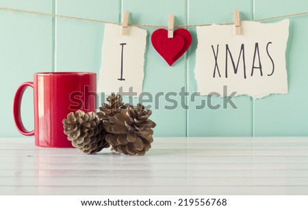 """I love xmas"" hanging on a rope with clothespins. A robin egg blue wainscot as background and a red mug and some pinecones on a white wooden table. Vintage Style. - stock photo"