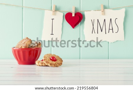 """I love xmas"" hanging on a rope with clothespins. A robin egg blue wainscot as background and a red bowl on a white wooden table. Vintage Style. - stock photo"