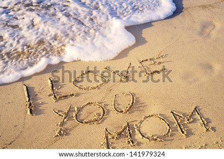 """""""I love you mom"""" written on sand. - stock photo"""