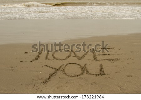 'I love you' signs drawn on the sand of a beach. - stock photo