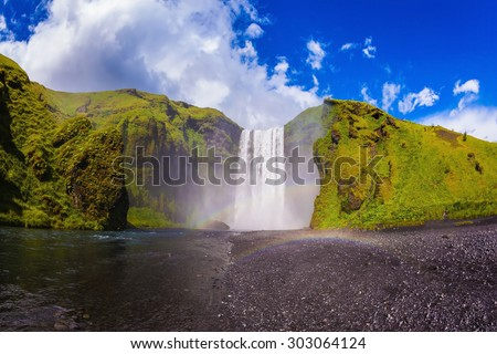 Iceland, waterfall Skogafoll summer, clouds of mist. Huge waterfall flowing from under a giant glacier - stock photo