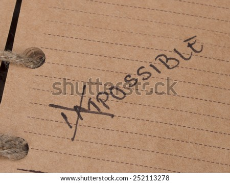 (IM)POSSIBLE text in the vintage notebook - stock photo