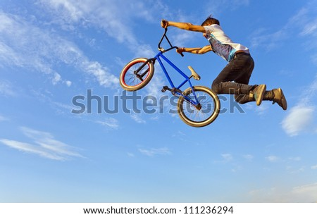 Image of teenager on a bicycle in a jump on a background blue sky. - stock photo