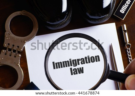 """Immigration law"" text with a man hold magnifying glass zoom on paper with pen, whistle, handcuff and a pair of black shoes on wooden table - law and enforcement concept - stock photo"