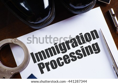 """Immigration processing"" text on paper with pen, whistle, handcuff and a pair of black shoes on wooden table - law and enforcement concept - stock photo"