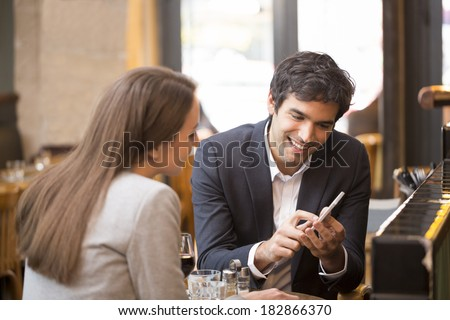 In a restaurant cheerful couple surfing the web, looking a photo on smartphone - stock photo