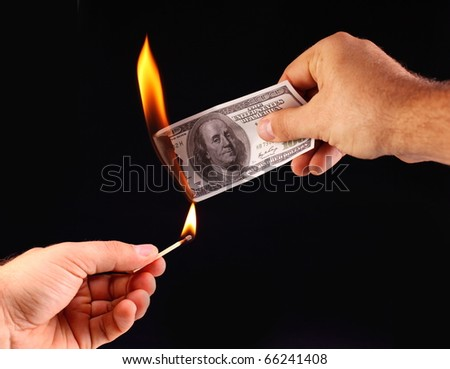 $ 100 in hand, set fire to a match. Isolated on a black - stock photo