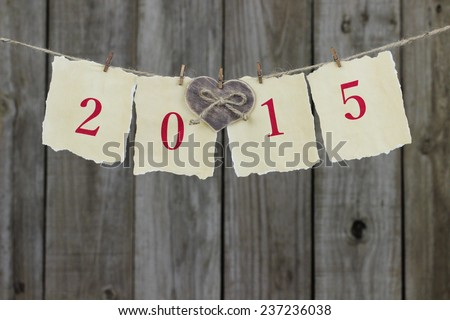 2015 in red on antique parchment paper sign with wood heart hanging on clothesline with wooden background - stock photo