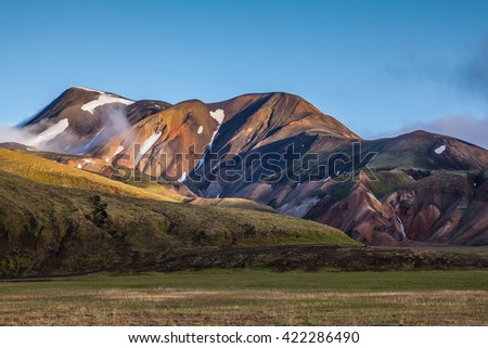 In the hollows of rhyolitic mountain snow. Above the source of hot water steam rises. Early summer morning in the National Park Landmannalaugar, Iceland - stock photo