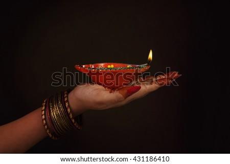 Indian girl's hand holding oil lamp  - stock photo