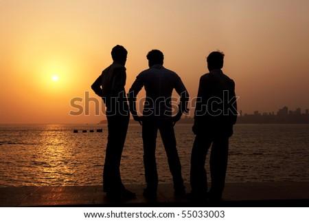 3 Indian guys watch the sun set over Mumbai. - stock photo