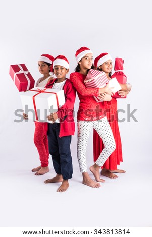 4 indian teenagers holding christmas gifts with santa hat on head, isolated on white background, standing close, indian kids and christmas, asian kids and christmas, isolated on white background - stock photo