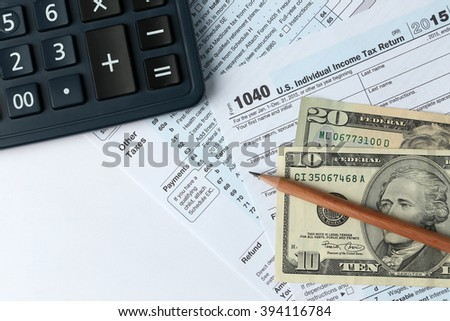 1040 Individual Income Tax Return Form for 2015 year with a pencil to fill in, calculator and dollar bills on the white desk, top view - stock photo