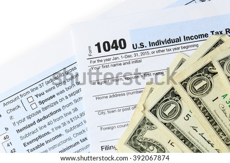 1040 Individual Income Tax Return Form for 21015 year with one hundred dollar bills on white background, close up