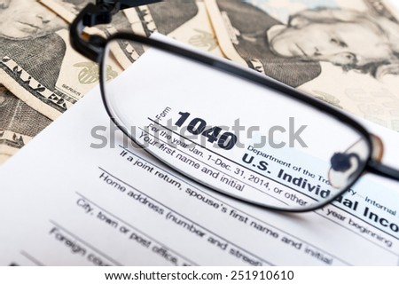 1040 individual tax return form close up, glasses and dollar bills - stock photo