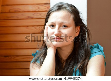 Indoor portrait of beautiful young woman with healthy glowing skin and light makeup.Skin care concept. Smiling woman touching her cheek and looking at a camera. - stock photo