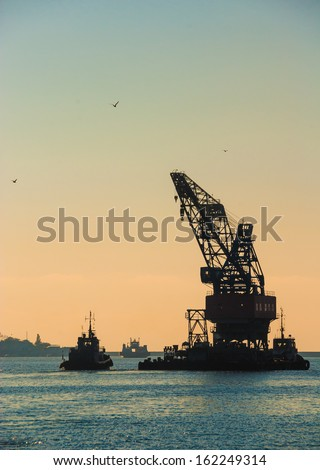 Industrial landscape - sea port at sunset. Construction works in the sea at the offshore platform. Skyline with silhouette of marine crane platform and barge. - stock photo