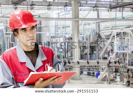 Industrial worker writes on a paper conditions in a filling line production of liquid detergent.Shallow doff
