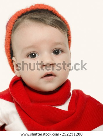 Innocent baby wearing a red hat and a muffler and looking adorable. Small kid dressed for winter, lovely newborn