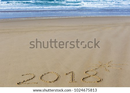 2018 inscription on wet beach sand and sea waves on background. Summer season holiday, vacation concept.