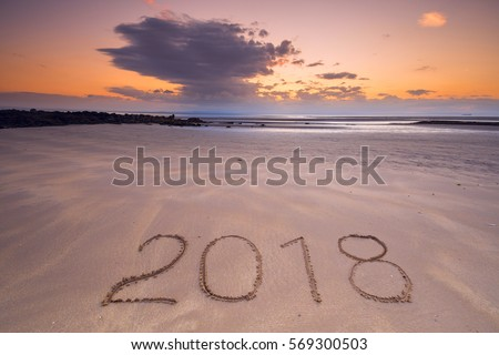 2018 inscription on wet sandy beach after ebb. Concept of celebrating the New Year.
