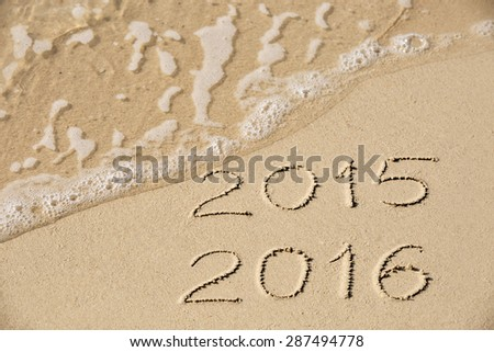 2015 2016 inscription written in the wet yellow beach sand being washed with sea water wave. Concept of celebrating the New Year at some exotic place - stock photo