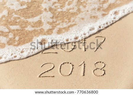 2017 2018  inscription written in the wet yellow beach sand being washed with sea water wave. Concept of celebrating the New Year at some exotic place