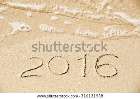 2016 inscription written in the wet yellow beach sand being washed with sea water wave. Concept of celebrating the New Year at some exotic place - stock photo